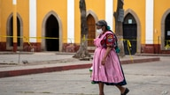 An indigenous woman wearing a protective mask walks near the cemetery amid the new coronavirus pandemic in Quetzaltenango,…