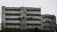 FILE - In this April 28, 2017 file photo, prison guards stand on the roof of the Ramo Verde military prison in Los Teques, on…