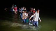 Migrant families, mostly from Central American countries, wade through shallow waters after being delivered by smugglers on…