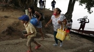 A Venezuelan family carries their belongings after crossing the Arauca River by boat to leave Venezuela, in Arauquita, Colombia…