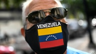 A man wears a face mask with the Venezuela flag, amid the spread of the new coronavirus, as he waits for hours to fill up his…