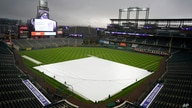 Grounds crew workers pull the tarpulin as a light rain descends on Coors Field Tuesday, April 6, 2021, before the Colorado…