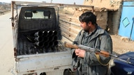 FILE - In this Dec. 19, 2020, file photo, an Afghan security official stands near a vehicle in which rockets were placed, in…