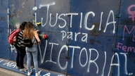 Young women place flowers on the perimeter wall of the Quintana Roo state offices sprayed with graffiti that reads in Spanish …