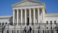 FILE - In this March 21, 2021, file photo people view the Supreme Court building from behind security fencing on Capitol Hill…
