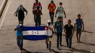Migrants walk with a Honduran flag, along a highway in hopes of reaching the distant United States, as they depart San Pedro…