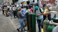 People wait with their empty oxygen tanks outside a refill store, to take home to family members with COVID-19 in Caracas,…