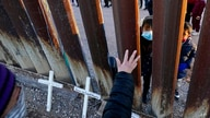 Vicky Chaidez waves to children on the Mexico side of the border fence at the start of a Las Posadas event with several asylum…