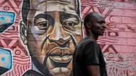 "A local resident stands next to a mural painted in June 2020 showing George Floyd with the Swahili word ""Haki"" or ""Justice"" in…"