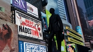 A statue of playwright and performer George M. Cohan stands in New York's Times Square in front of billboards for Broadway…