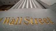 FILE - In this Nov. 5, 2020 file photo, a sign for Wall Street is carved in the side of a building, in New York. Stocks are off…