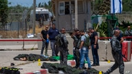 Israeli forces inspect the scene of a shooting attack where bodies of two Palestinian gunmen, killed by Israeli border police,…