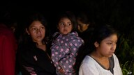 Migrants from Guatemala and Honduras stand on the banks of the Rio Grande River after being smuggled on an inflatable raft in…