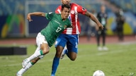 Bolivia's Roberto Fernandez, left, dribbles past Paraguay's Hector Martinez during a Copa America soccer match at Olimpico…