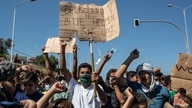 """Migrants take part in a rally as the banner reads in German """"Germany Please Help Us"""" near Mytilene town, on the northeastern…"""