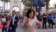 Los Angeles County supervisor Hilda Solis wears a mask as she arrives in a news conference at Universal Studios in Universal…
