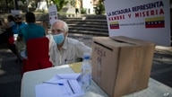 """A volunteer waits for voters under a sigan reading in Spanish """"Dictatorship Means Hunger and Misery"""" during a consultation…"""