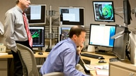 National Hurricane Center Deputy Director Ed Rappaport, left, observes hurricane specialist Dan Brown as he conducts a…