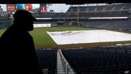 A worker looks at the tarp covering the field before a baseball game between the Washington Nationals and the San Francisco…