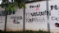 """A wall that is defaced with graffiti with one message that once read in Spanish: """"Resist Nicaragua"""", was overpainted by another…"""