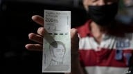 A man shows a new 200,000 Bolivar bill after withdrawing it from a bank in Caracas, Venezuela, Tuesday, March 16, 2021. The…