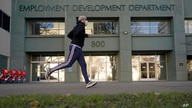FILE - In this Dec. 18, 2020, file photo a runner passes the office of the California Employment Development Department in…