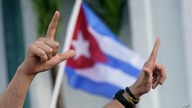 """Demonstrators sign the letter """"L,"""" for liberty and wave flags, Wednesday, July 14, 2021, in Miami's Little Havana neighborhood,…"""