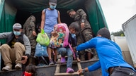 FILE - In this Jan. 19, 2021 file photo, a Honduran migrant child is helped off an army truck after being returned to El…