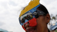 A supporter of Venezuela's Congress President Juan Guaidó, who declared himself interim president of the country, wears a map…