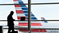 FILE - In this Jan. 25, 2016, file photo, a passenger talks on the phone as American Airlines jets sit parked at their gates at…