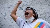 A woman shouts outside the Colombian consulate in Caracas, Venezuela, Friday, May 7, 2021, during duel gatherings of members of…