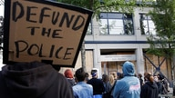 """A protester holds a sing that reads """"defund the police"""" after Seattle Police vacated the department's East Precinct in Seattle"""
