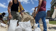Residents fill and collect sand bags before the expected arrival of Hurricane Isaias in Doral