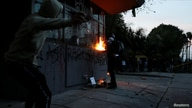 People vandalize the exterior of a police station during a protest after a man, who was detained for violating social distancing rules, died from being repeatedly shocked with a stun gun by officers, according to authorities, in Bogota