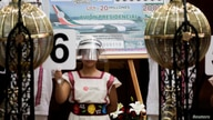 A lottery tickets for the raffle of a presidential luxury plane is seen as a girl holds a sign of number 6 during a lottery raffle for the value of the last president's luxury plane at the National Lottery building in Mexico City