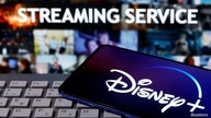 "FILE PHOTO: Smartphone with displayed ""Disney"" logo is seen on the keyboard in front of displayed ""Streaming service"" words in this illustration"