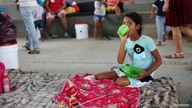 A Venezuelan migrant girl takes her food inside a coliseum where a temporary camp is installed, after fleeing her country due to military operations, according to the Colombian migration agency, in Arauquita