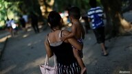 A young mother from Honduras is seen on a day out at the river in Tenosique