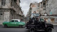 A special forces vehicle passes by a vintage car in downtown Havana