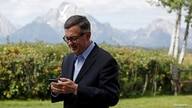 """FILE PHOTO: Federal Reserve Vice Chair Richard Clarida reacts as he holds his phone during the three-day """"Challenges for Monetary Policy"""" conference in Jackson Hole"""