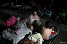 People rest at a makeshift camp outside their apartment building after an earthquake in Yauco, Puerto Rico