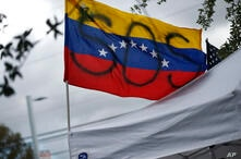 """A Venezuela flag is flown with a painted """"SOS"""" during a rally at the El Arepazo Doral Venezuelan restaurant, in Doral, Fla., May 1, 2019."""
