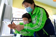 A child wearing a face mask cleans her hands at a kindergarten that has resumed operation following the coronavirus disease …
