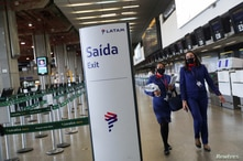 FILE PHOTO: Latam Airlines employees walk at the company's check-in hall at Guarulhos International airport as air traffic is…
