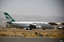 FILE - In this March 1, 2015 file photo, a plane from the Iranian private airline, Mahan Air lands the international airport in…