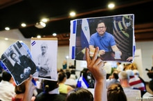 A woman holds up a picture of the journalist Miguel Mora, the director of 100% Noticias who was arrested in December 2018 after…