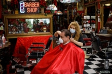 A hairdresser wearing a protective mask cuts the hair of a man at a barber shop, as Miami-Dade County eases some of the…