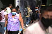 People walk on a street as the city allowed some businesses to reopen on Wednesday following a fall in daily deaths due to the…