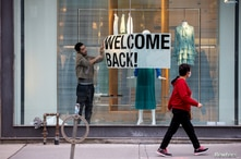 FILE PHOTO: An employee at Zara puts up a sign during a phased reopening from the coronavirus disease (COVID-19) restrictions…