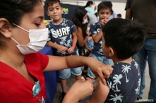 FILE PHOTO: A child receives a vaccination as part of the start of the seasonal flu vaccination campaign as a preventive…